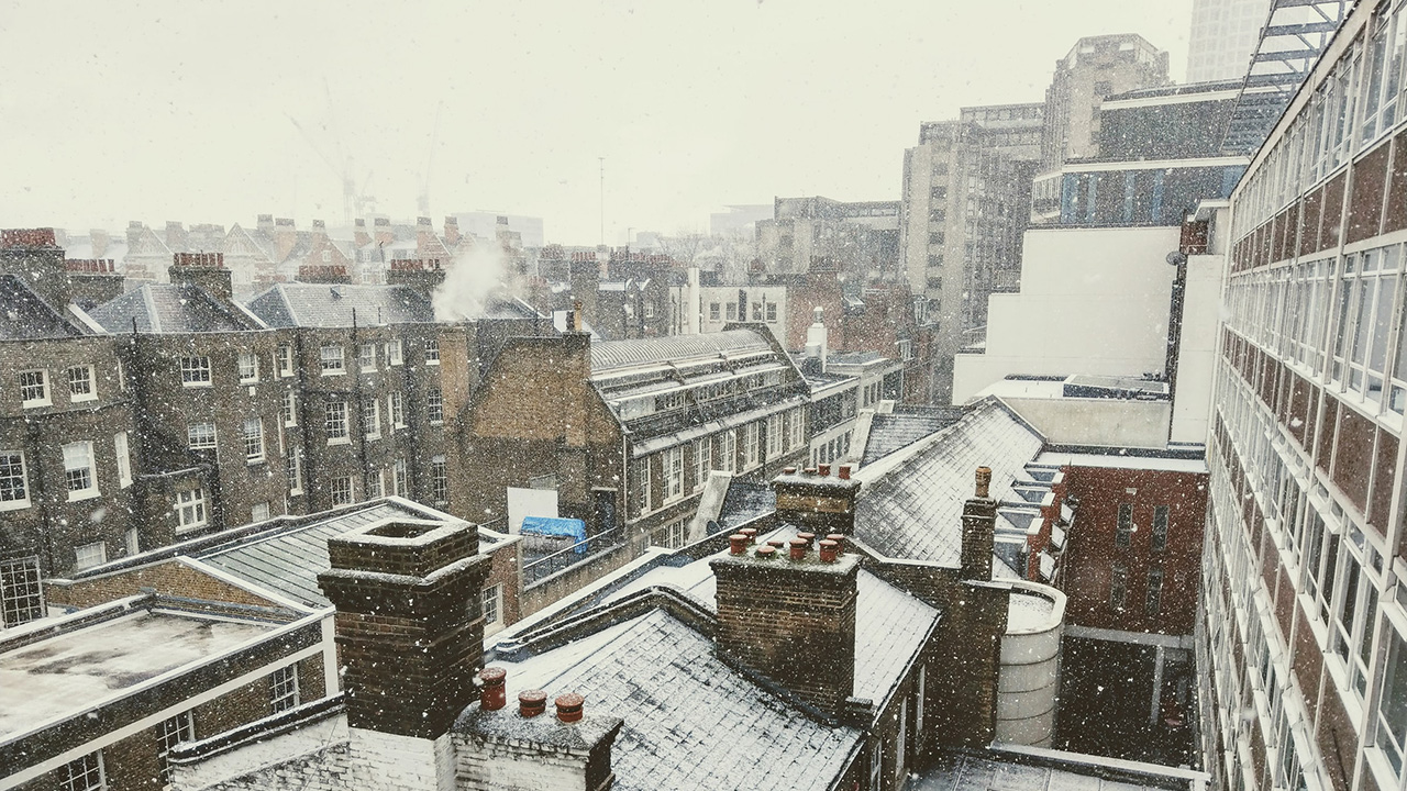 Row of terrace house rooftops covered in snow