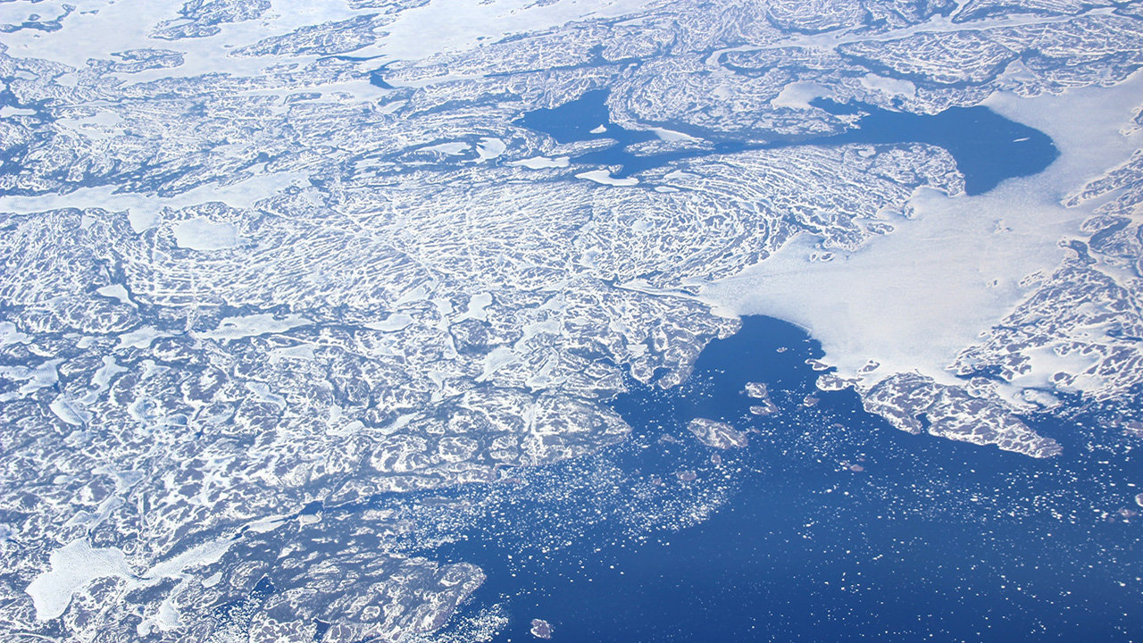 Artic circle viewed from above, through a layer of semi-transparent clouds
