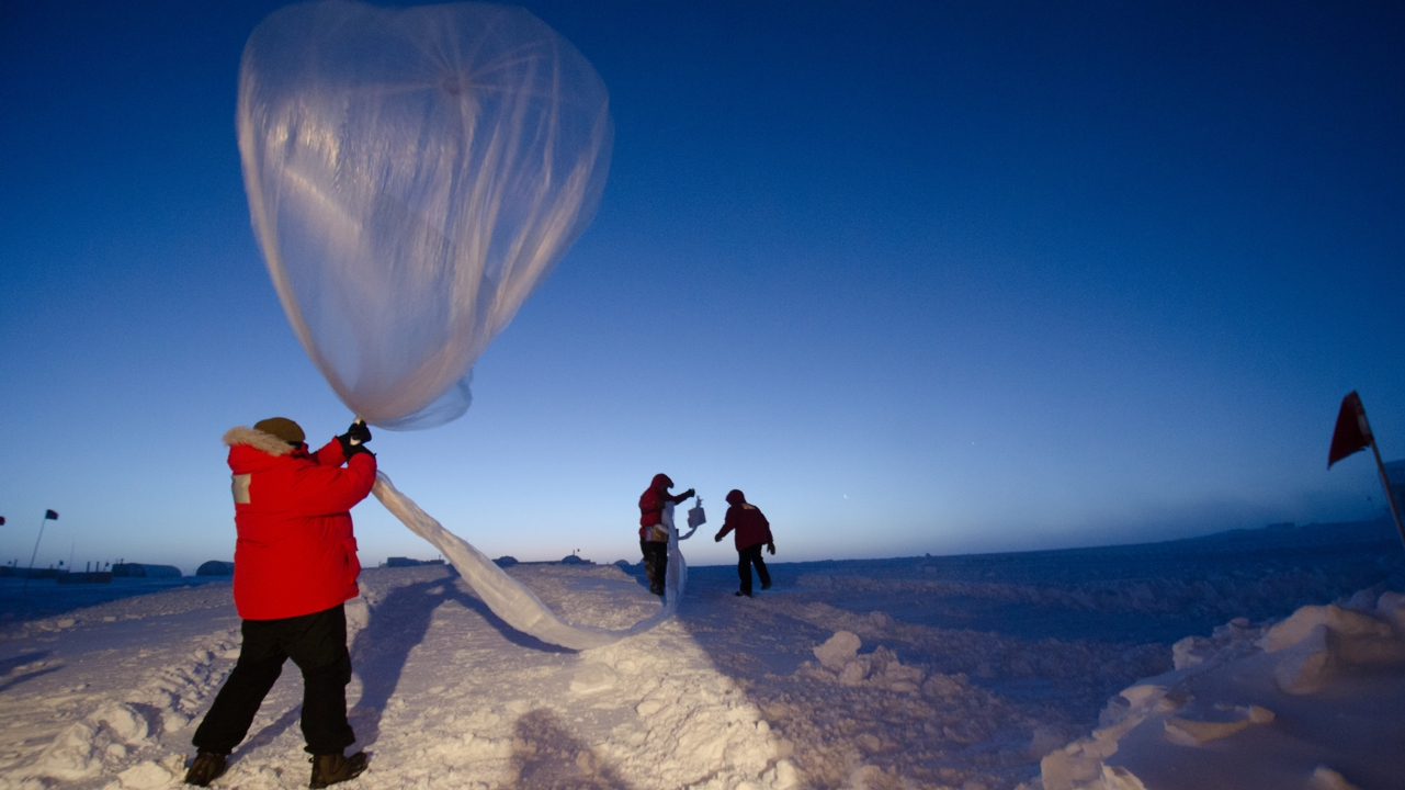 Person wearing thick orange coat holds a large balloon filled with helium, they stand on snowy ground.