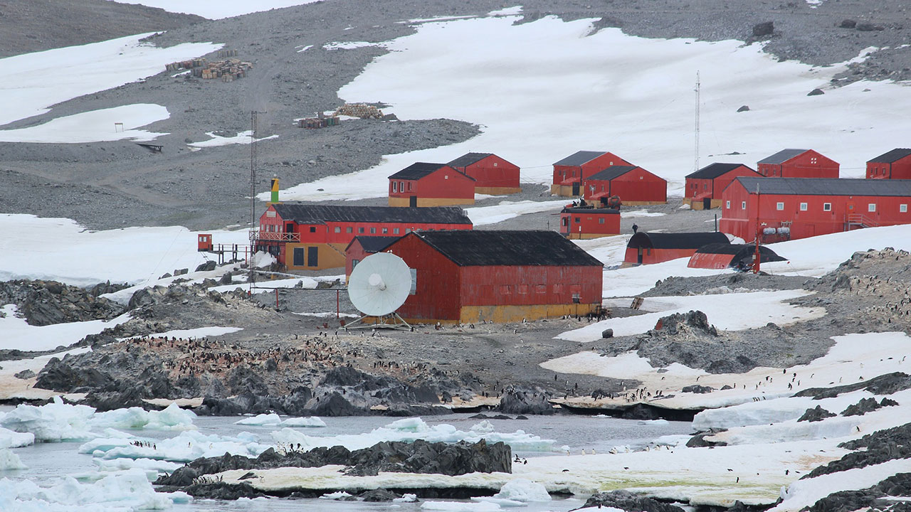Red buildings on grey, rocky land, with patches of ice nearby. There is a white, circular dish in the centre.