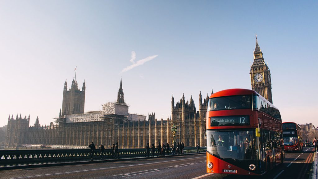 Red London bus moves along a quiet road. Large yellow brick buildings in the distance, including Big Ben.