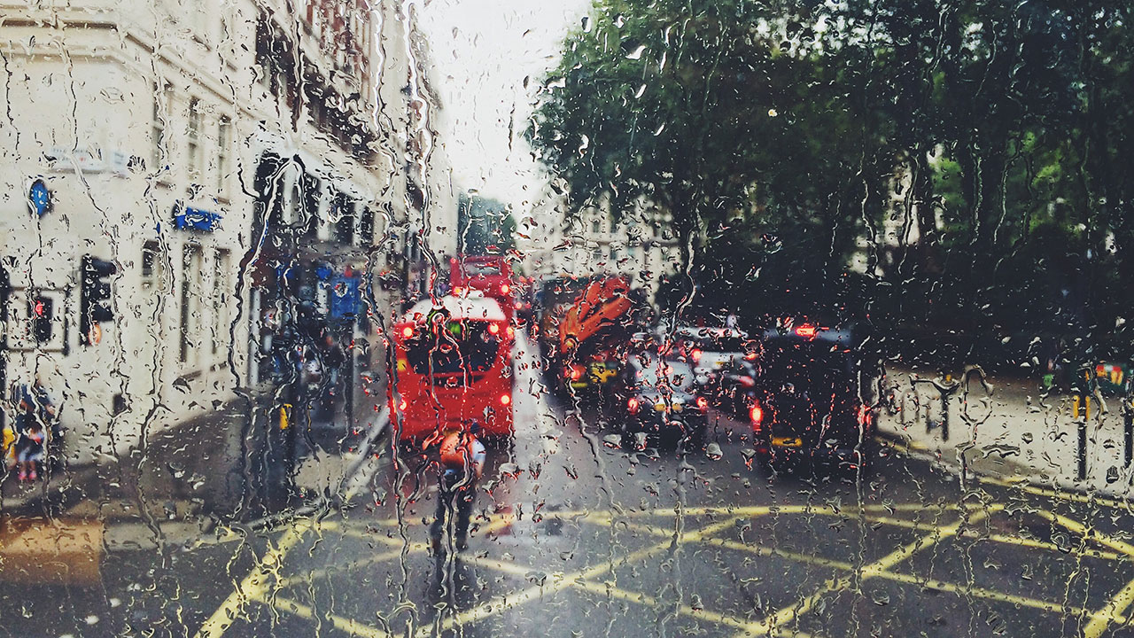 Red bus and man wearing orange jacket riding a bike travel down a road, rain droplets distort the view