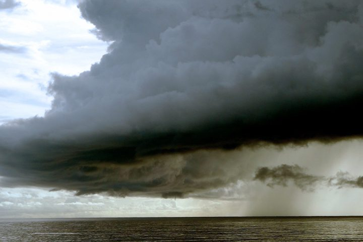 Large, dark cloud looms over the sea.