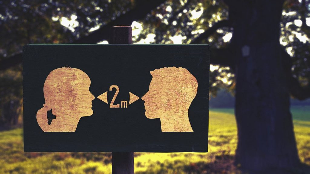 Public sign showing two silhouetted people and encouraging a two meter distance between them