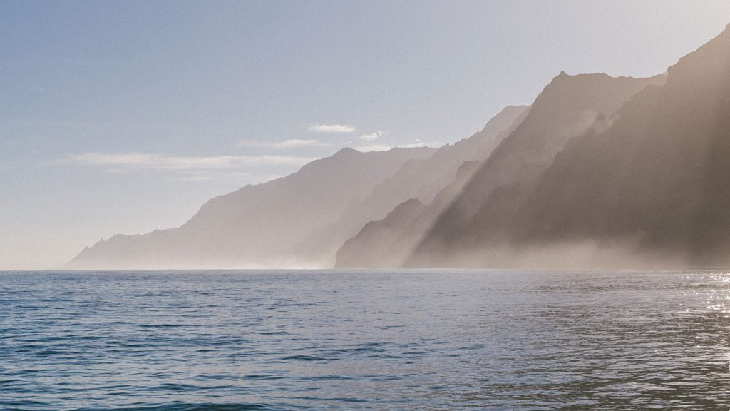 Mist rises off blue ocean, with sea cliffs in the distance