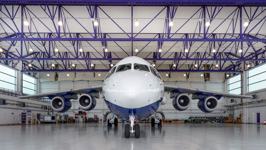 White and blue aircraft inside a large hangar