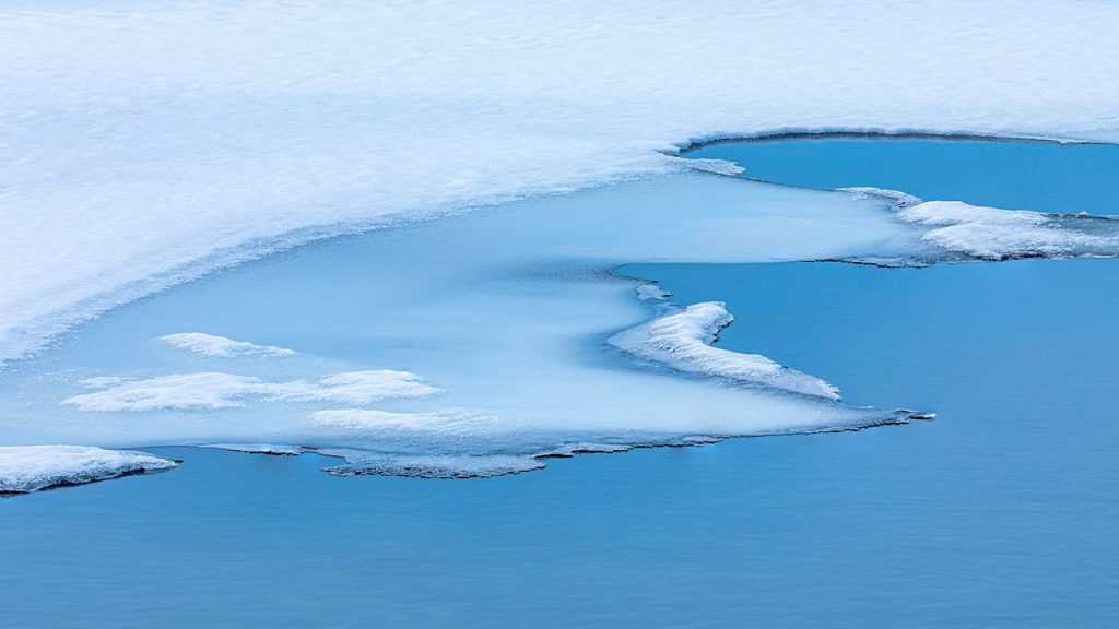 Large white sheet of ice sits on top of a blue body of water