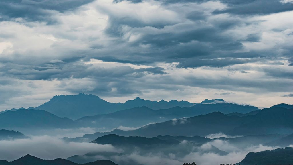 Grey clouds loom over silhouetted mountains