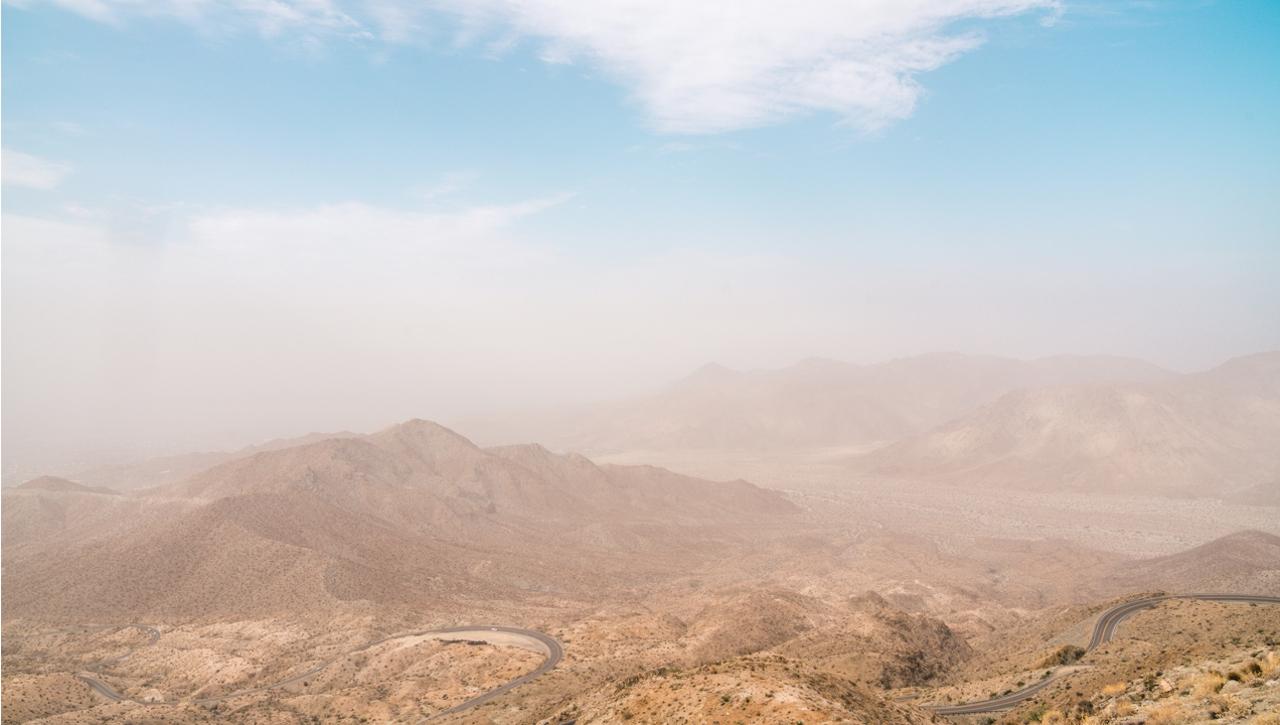 Dust swirls over sand dunes below a light blue sky.