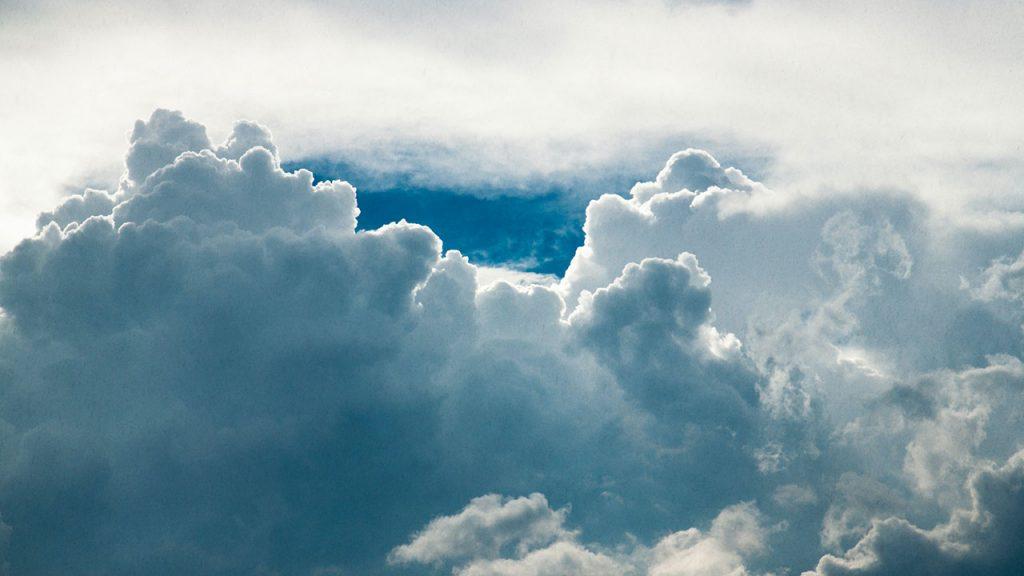 Fluffy, white clouds in a blue sky
