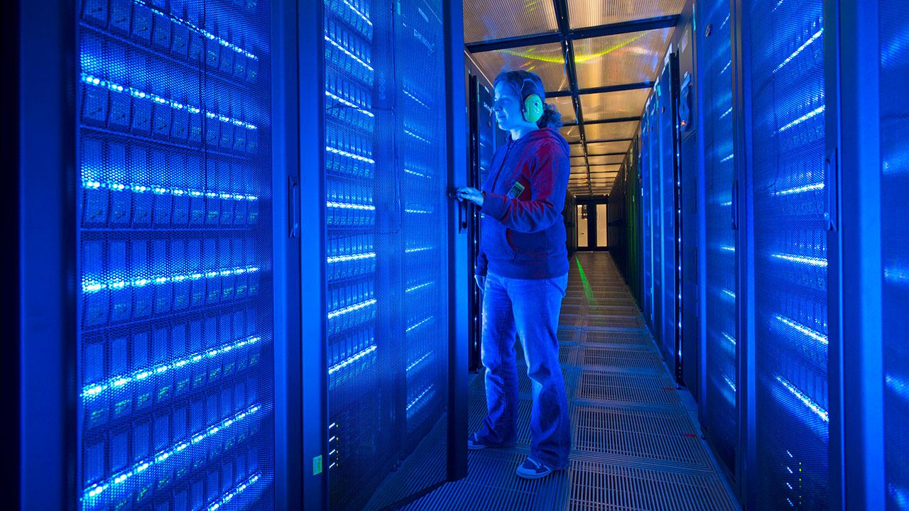 Woman wearing earphones stands in corridor between electric blue illuminated computer hardware