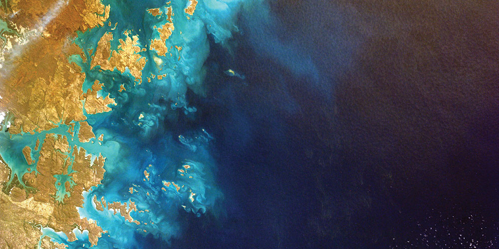 Satellite view of a golden coastline, next to a vivid blue ocean