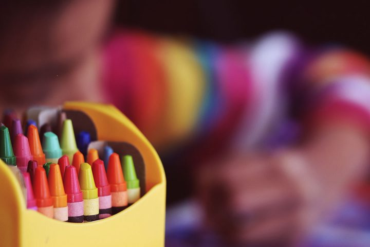 Multi-coloured crayons inside a yellow tub