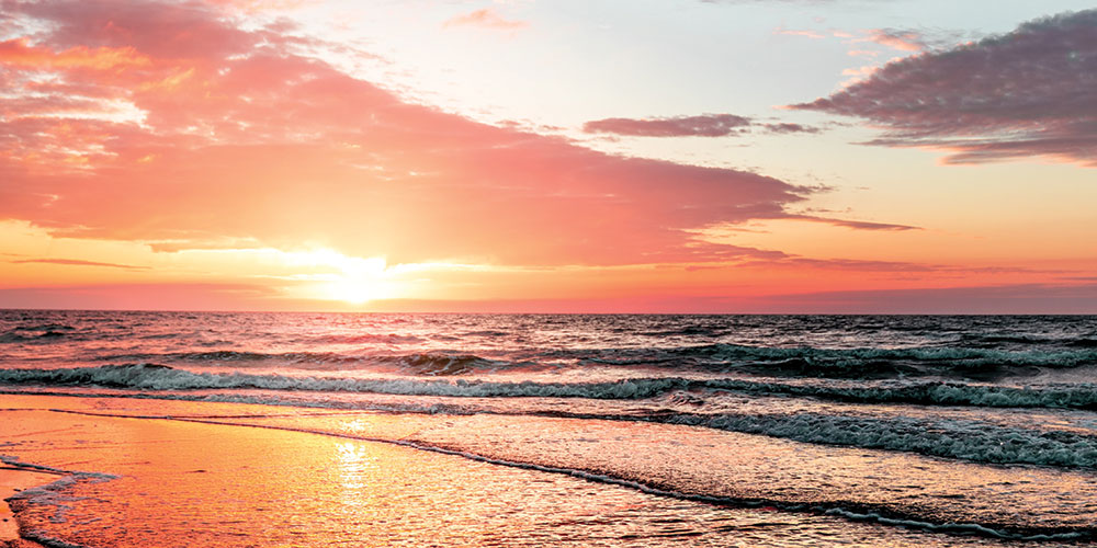Orange sunset behind a sandy beach with gentle waves lapping at the shore