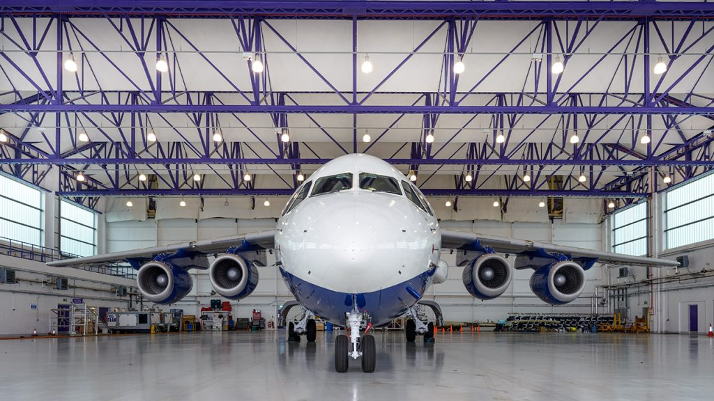 Front view of a large, white aircraft inside a large hangar