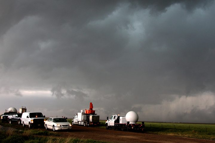 White cars towing round, white radar equipment, in front of a dark, grey, cloudy sky.