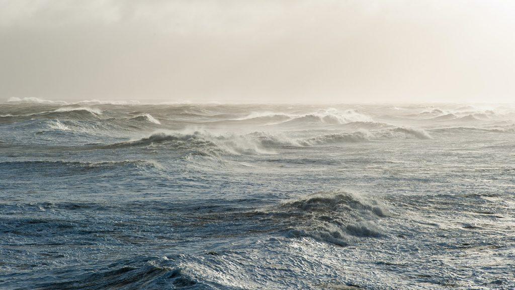 Ocean waves beneath a hazy, clear horizon