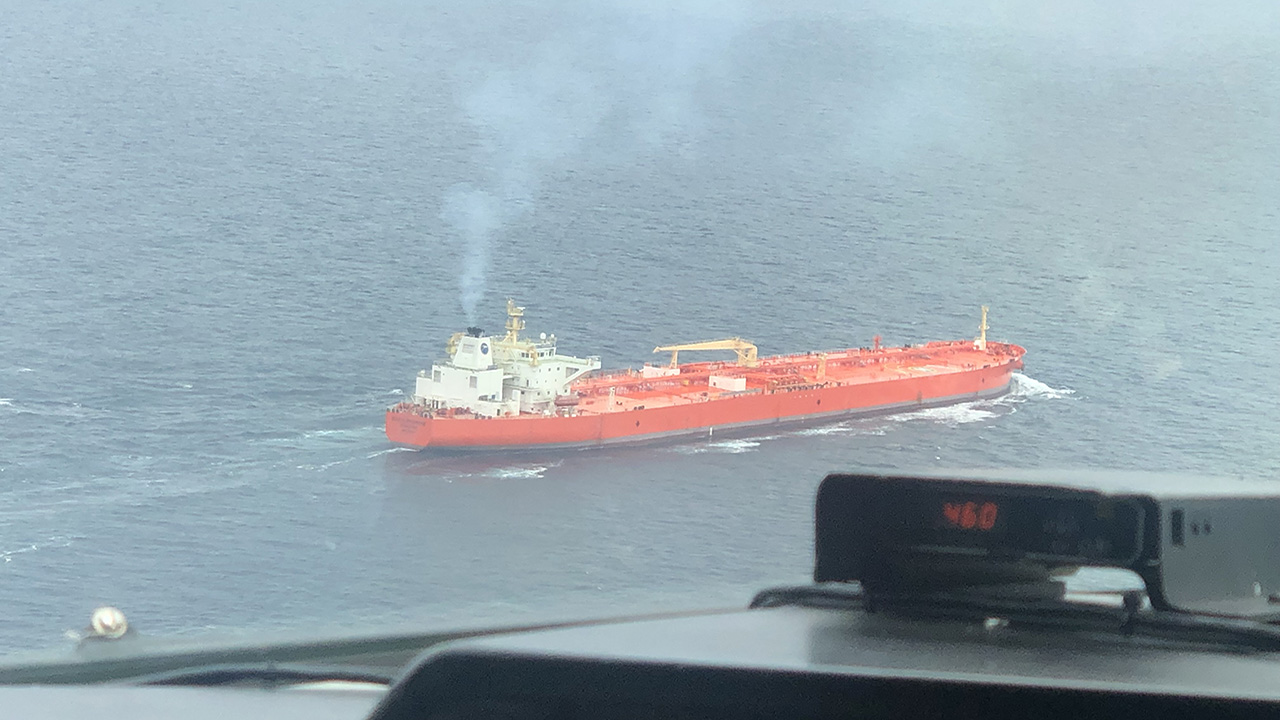 Red cargo ship emits exhaust plume and is seen from above from the FAAM aircraft