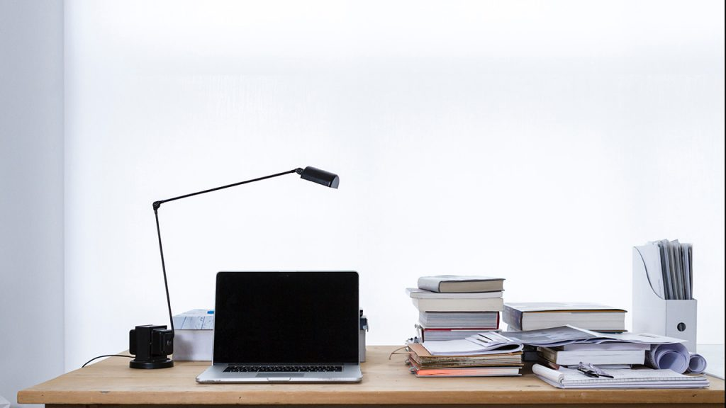 Wooden desk with laptop, reading lamp and piles of books.