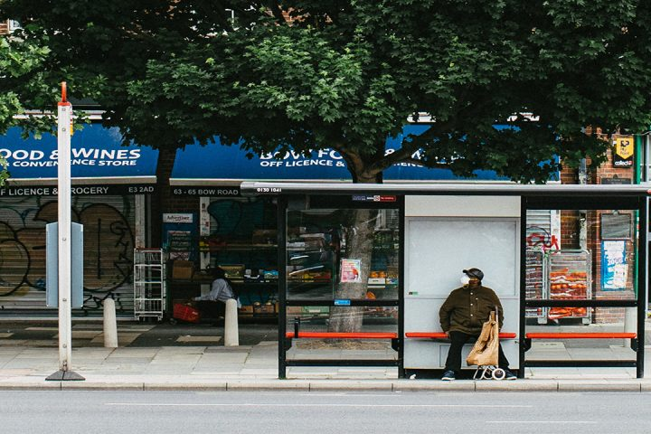 Man wearing a face mask, sat at a bus stop on a tree-lined street with shops