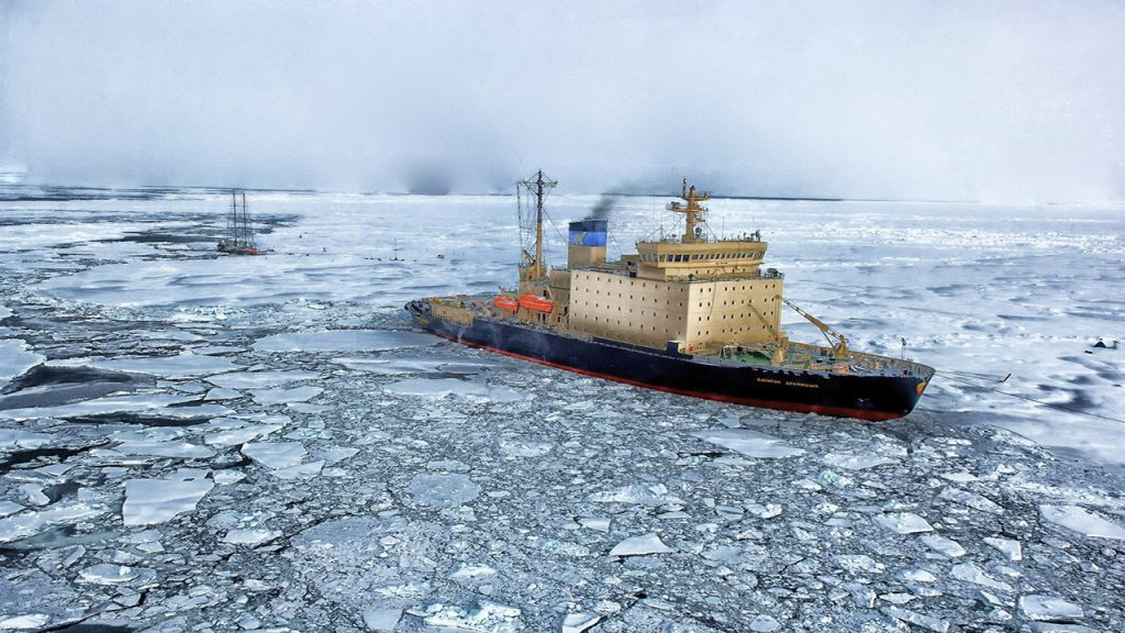 Large ship breaks through cracked ice in the Arctic sea
