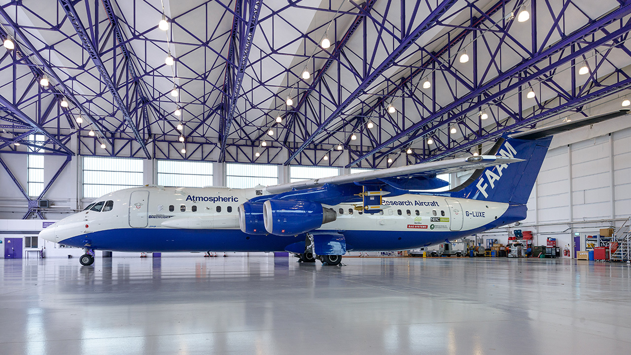 A large blue and white aircraft is parked inside a hangar with a shiny grey floor