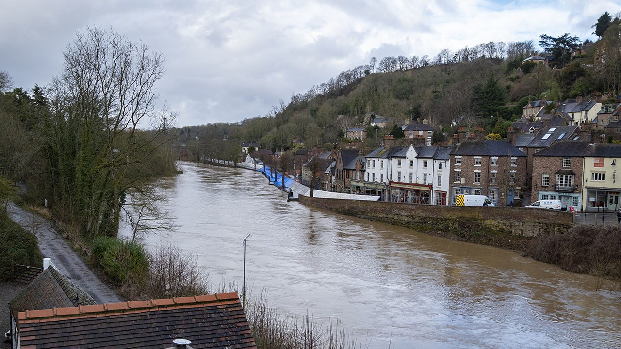 Brown river water flows through small village, with flood barriers along the road