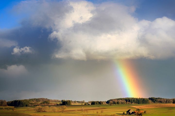 Cloudy blue sky with a rainbow, over a couple of fields and woodland