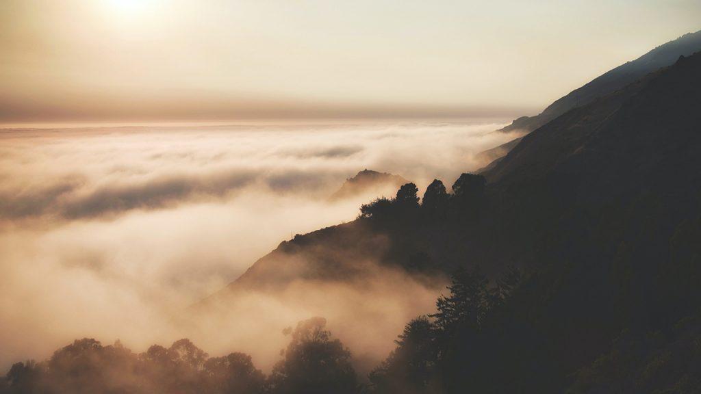 Low-lying clouds wrap around a dark hillside