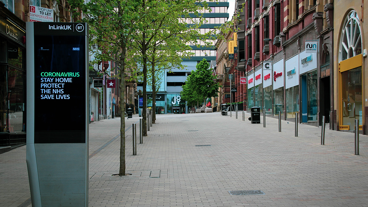 Empty pedestrianised high street, lined with shops.
