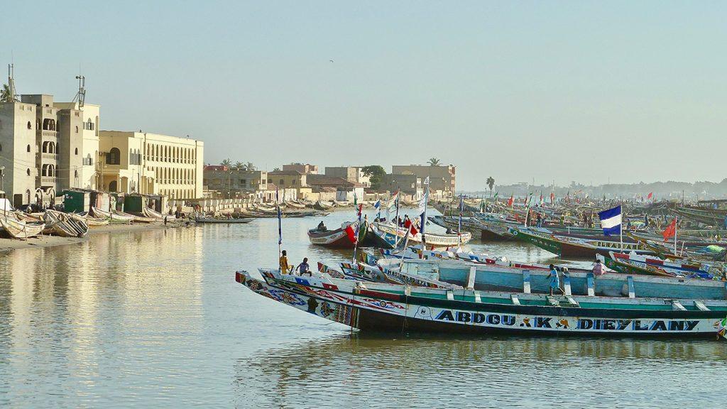 Long fishing boats float in harbour, beside seaside buildings in Senegal