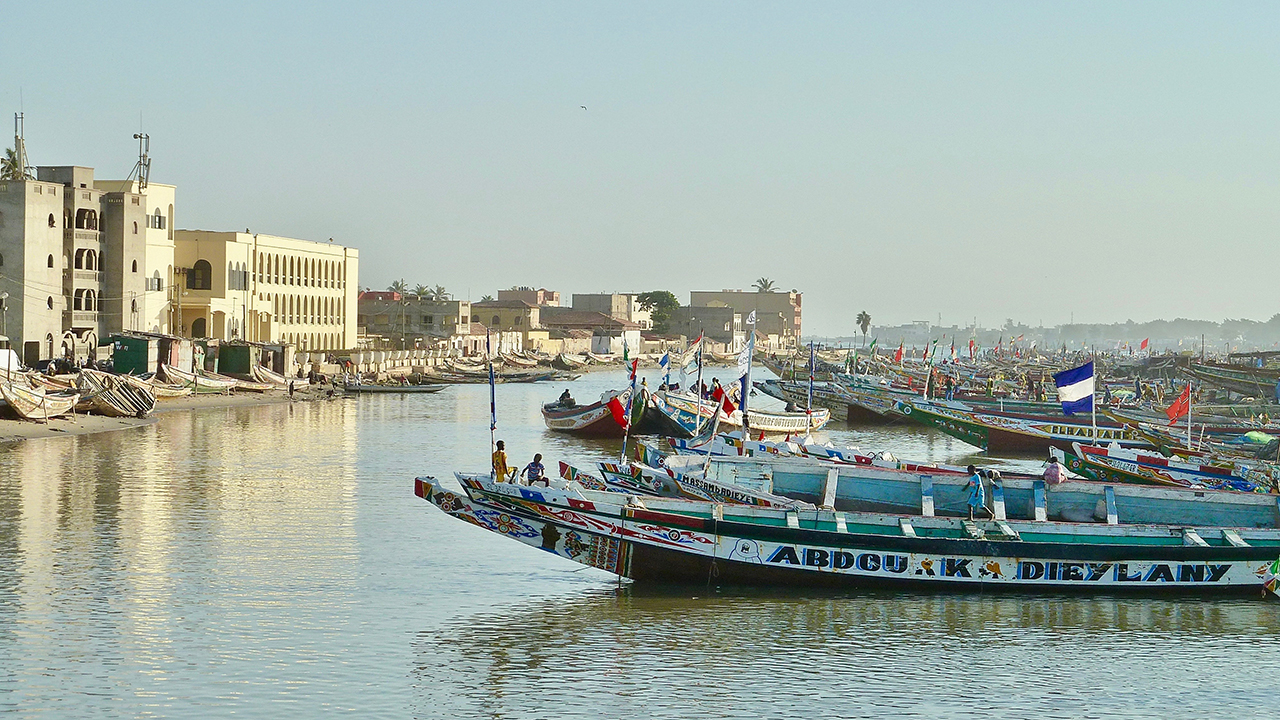 Long fishing boats float in harbour, beside seaside buildings in Senegal