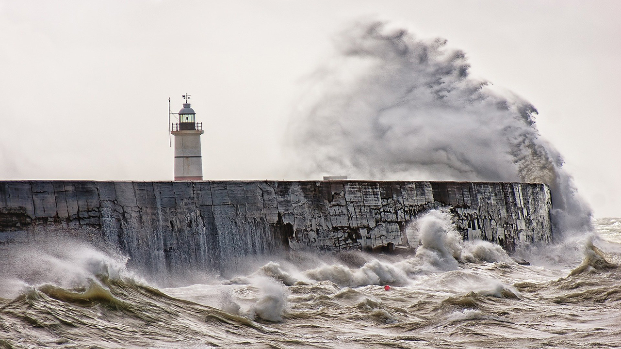 A wave hits a grey sea wall and sprays up in the air next to a lighthouse