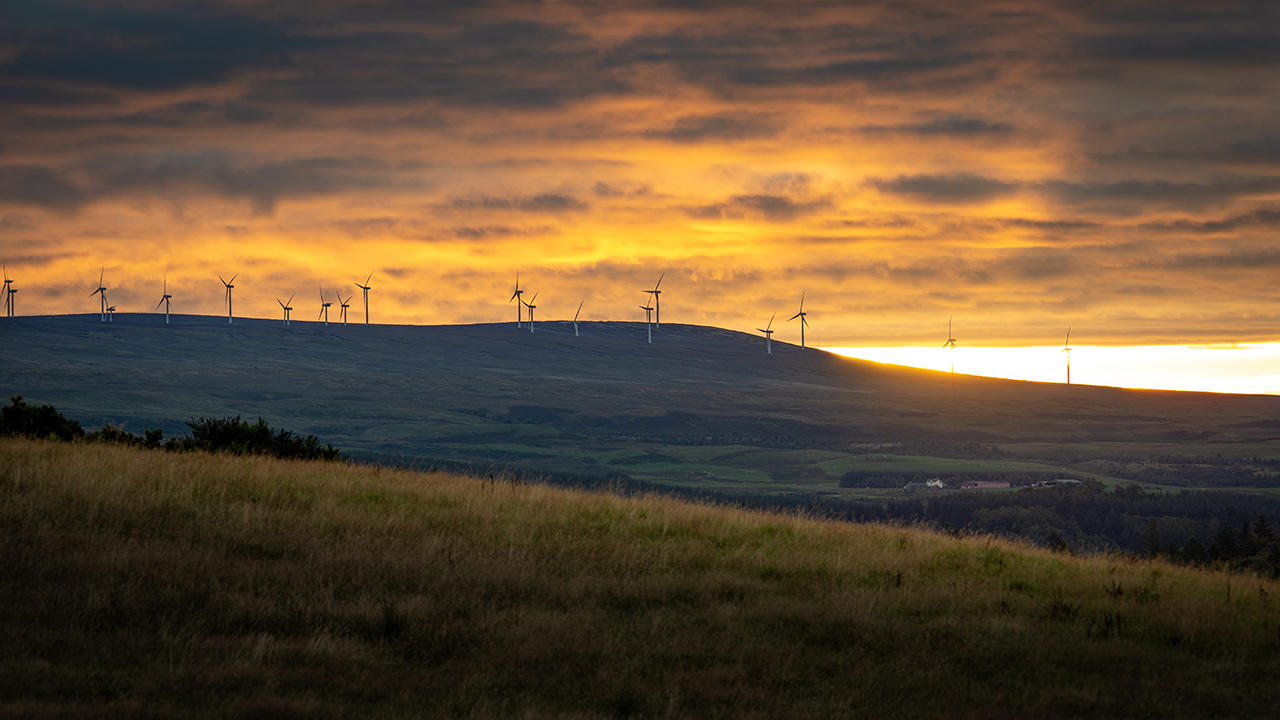 Rolling hills with wind turbines on the horizon, a sunset creates a vivid yellow sky.