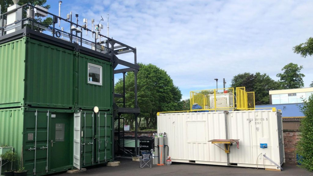 Three shipping containers adorned with scientific instruments below a blue sky.
