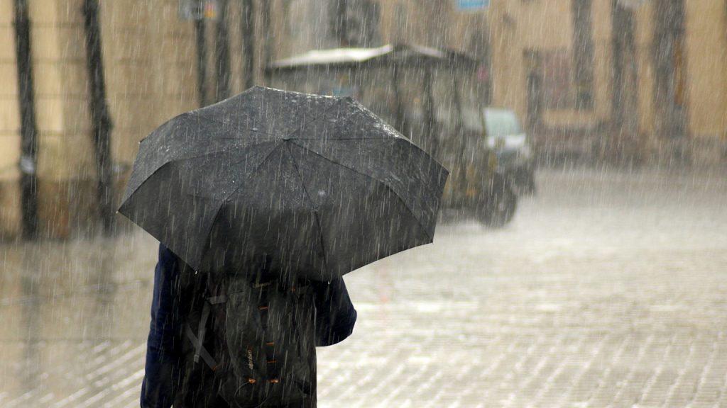 Person holds black umbrella in heavy rain