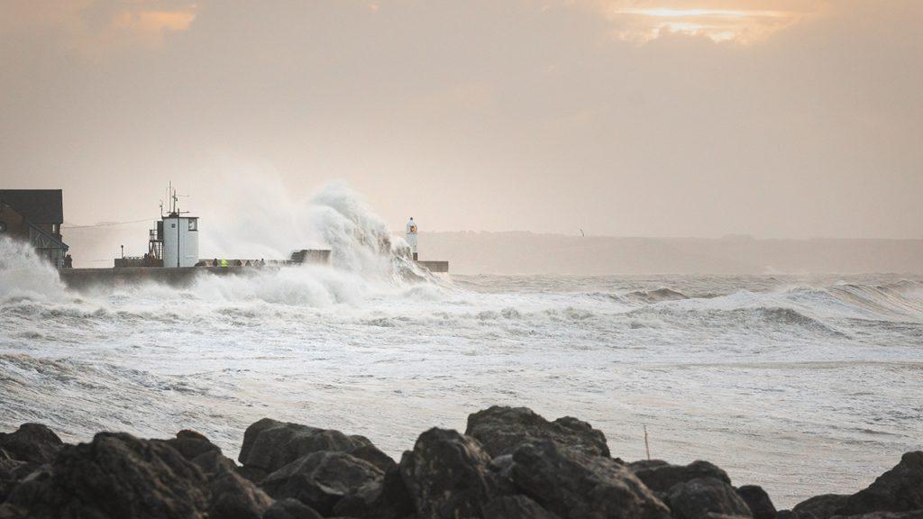 White waves crash against coastal peninsula