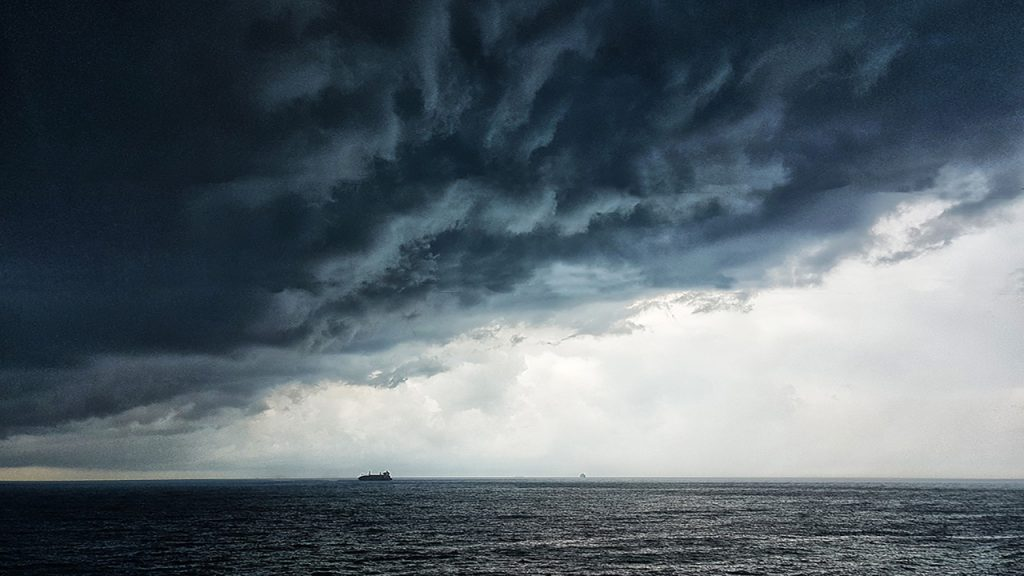 Large dark blue and grey storm cloud above a ship on the sea