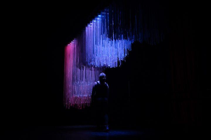 Person walks underneath hanging art exhibition. Twenty-six coloured stripes illuminate dangling plastic ribbons.